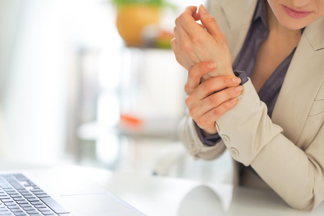 Frau, die ihr Handgelenk hält, nachdem Schmerz beim Schreiben erfahren worden ist.