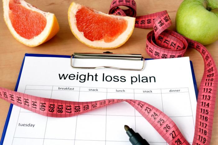 Presse-papiers avec un plan de perte de poids, ruban à mesurer et fruits.