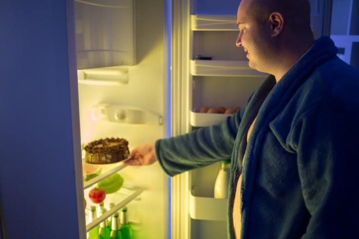 Người đàn ông lấy bánh từ tủ lạnh vào ban đêm.