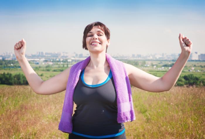 Một người phụ nữ hạnh phúc tập thể dục bên ngoài.