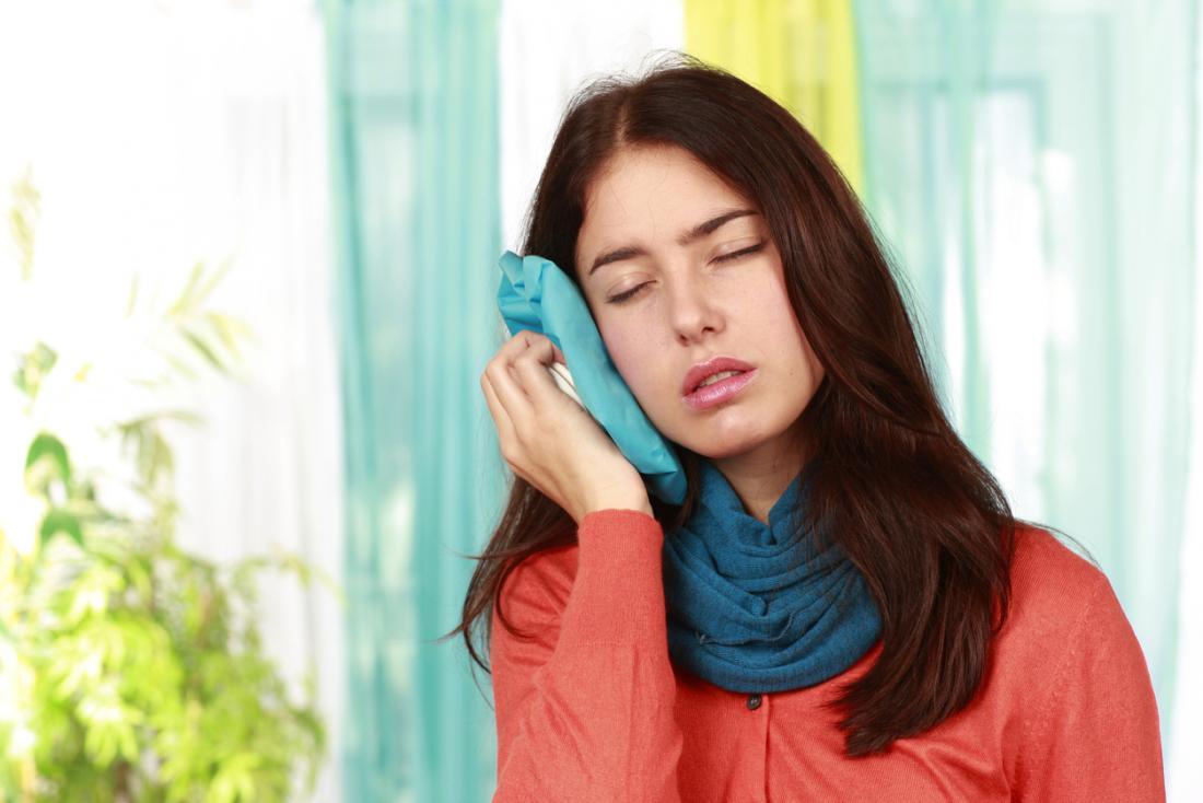 donna con impacco di ghiaccio all'orecchio