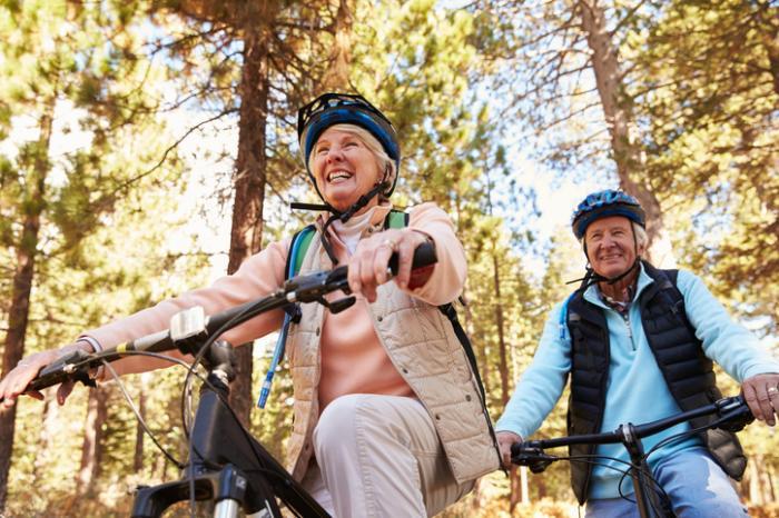 [felice coppia di anziani in bicicletta nei boschi]