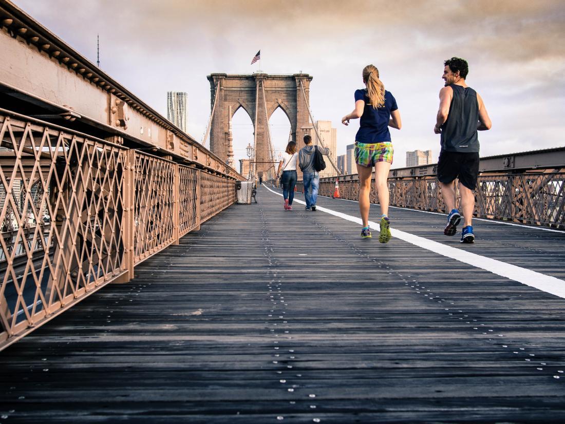 persone che fanno jogging e camminano su un ponte