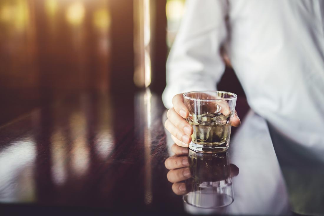 osoba trzyma kieliszek alkoholu
