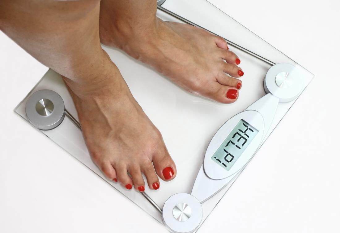 una donna che si pesa su una bilancia