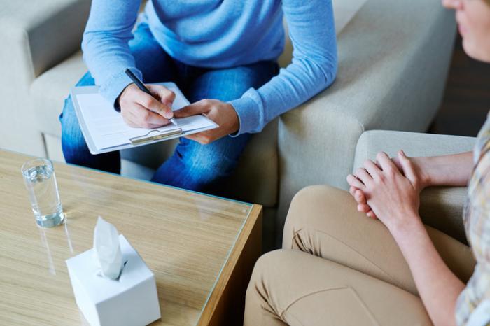 Un thérapeute prend des notes avec un patient.
