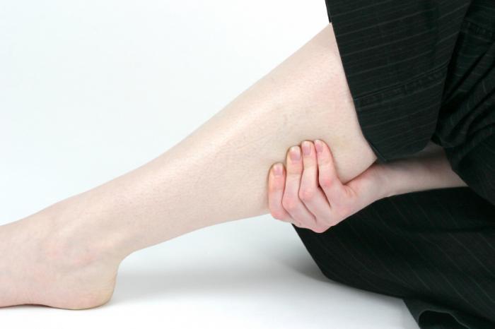 жена, която държи болезнен долен крак