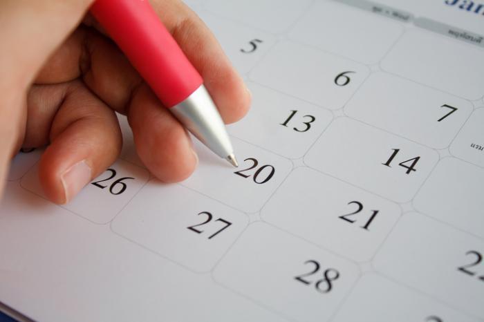 [Frau füllt Kalender aus]