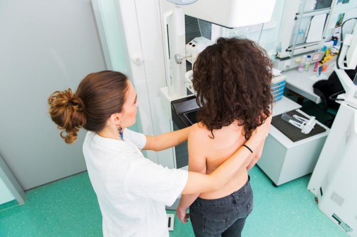 [Frau wird von einem Arzt durch ein Mammogramm geführt]