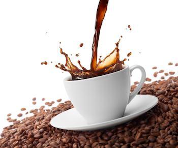 Kawa jest wylana na filiżankę, która siedzi na łóżku ziaren kawy