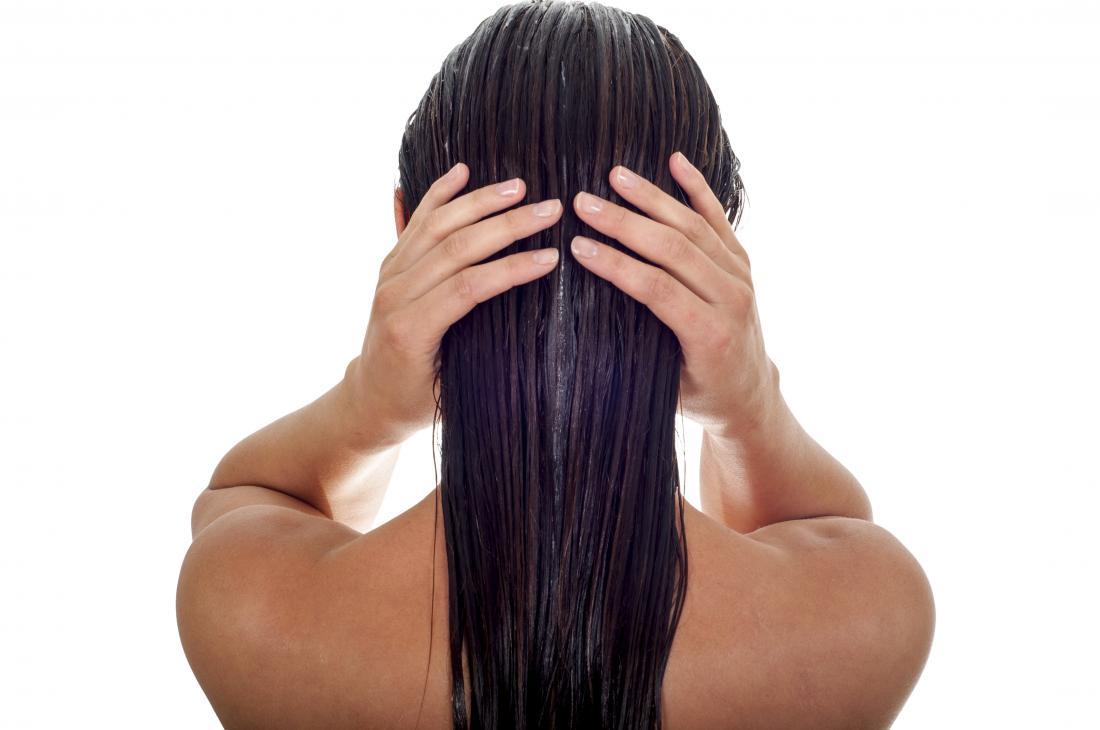 Laufendes Avocadoöl der Dame durch ihr Haar