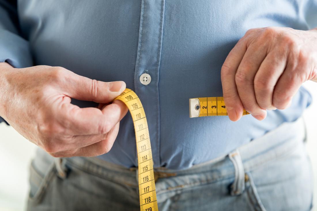 homem sênior, verificando a circunferência da cintura