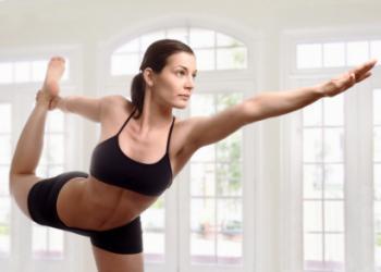 Жената балансира акробатично на единия крак.