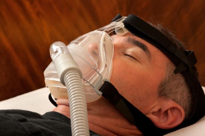männlicher Schlafapnoe-Patient, der einen kontinuierlichen positiven Atemwegsdruck erhält