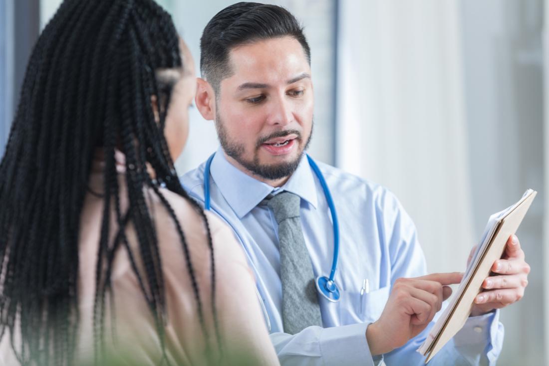 Млад мъжки лекар, който обсъжда резултатите с пациентката.