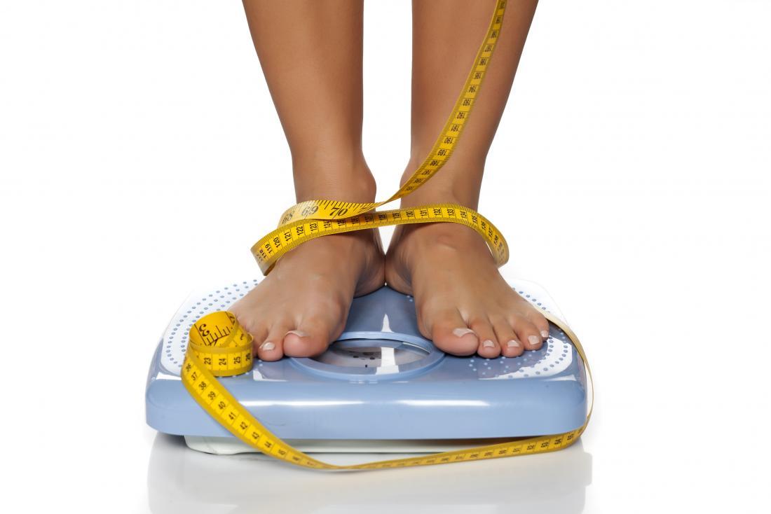mulher em escala com fita métrica em torno de pernas