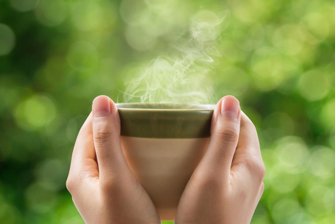 une femme tenant une tasse de thé