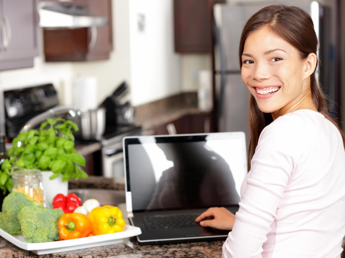 [mutfakta onu laptop üzerinde genç kadın]