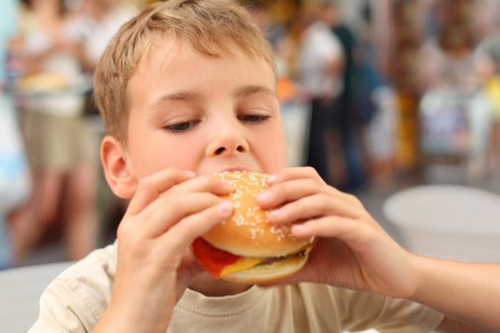 menino comendo hambúrguer