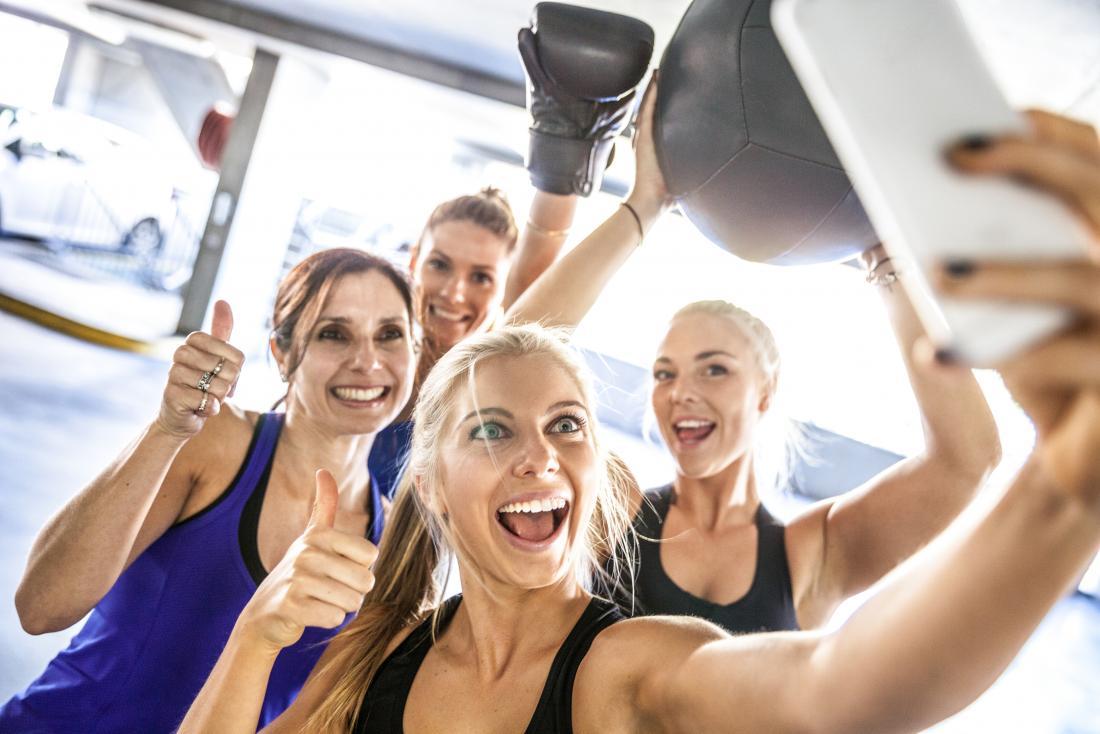 bạn bè chụp ảnh tự sướng trong phòng tập thể dục