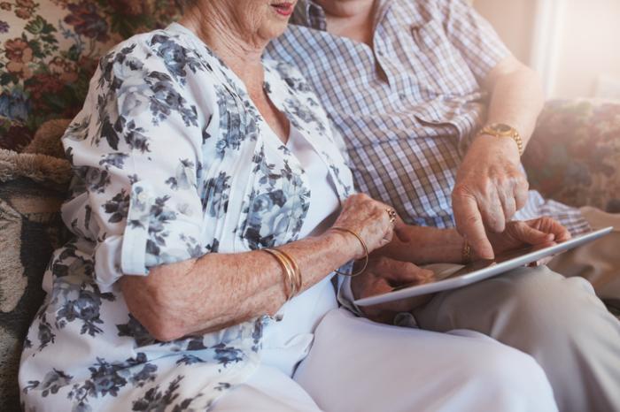 [casal sênior olhando para tablet]