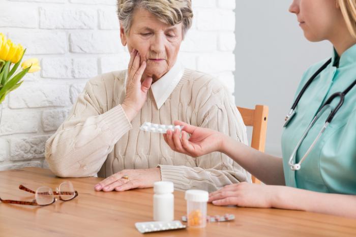 [infermiera che dà le medicine di Alzheimer alla donna anziana]
