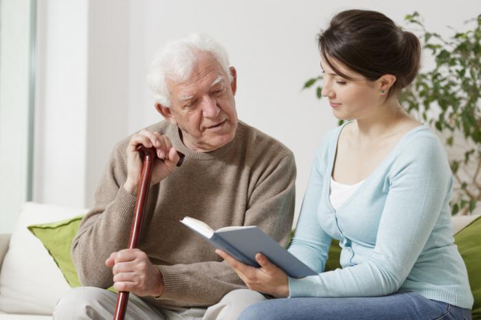 [badante che legge un uomo anziano un libro]