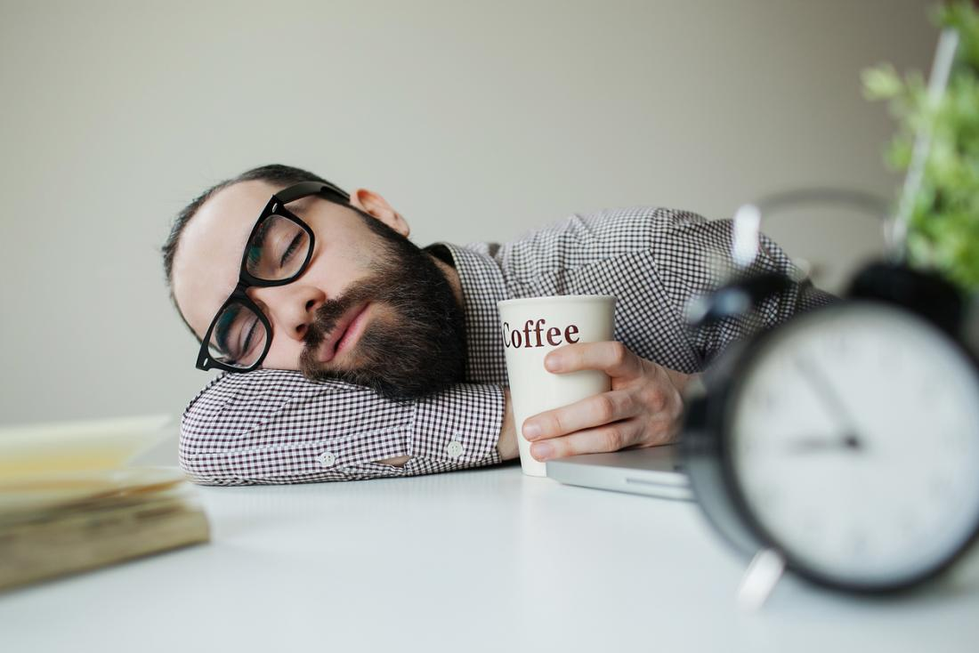 човек с очила, спящи на бюро