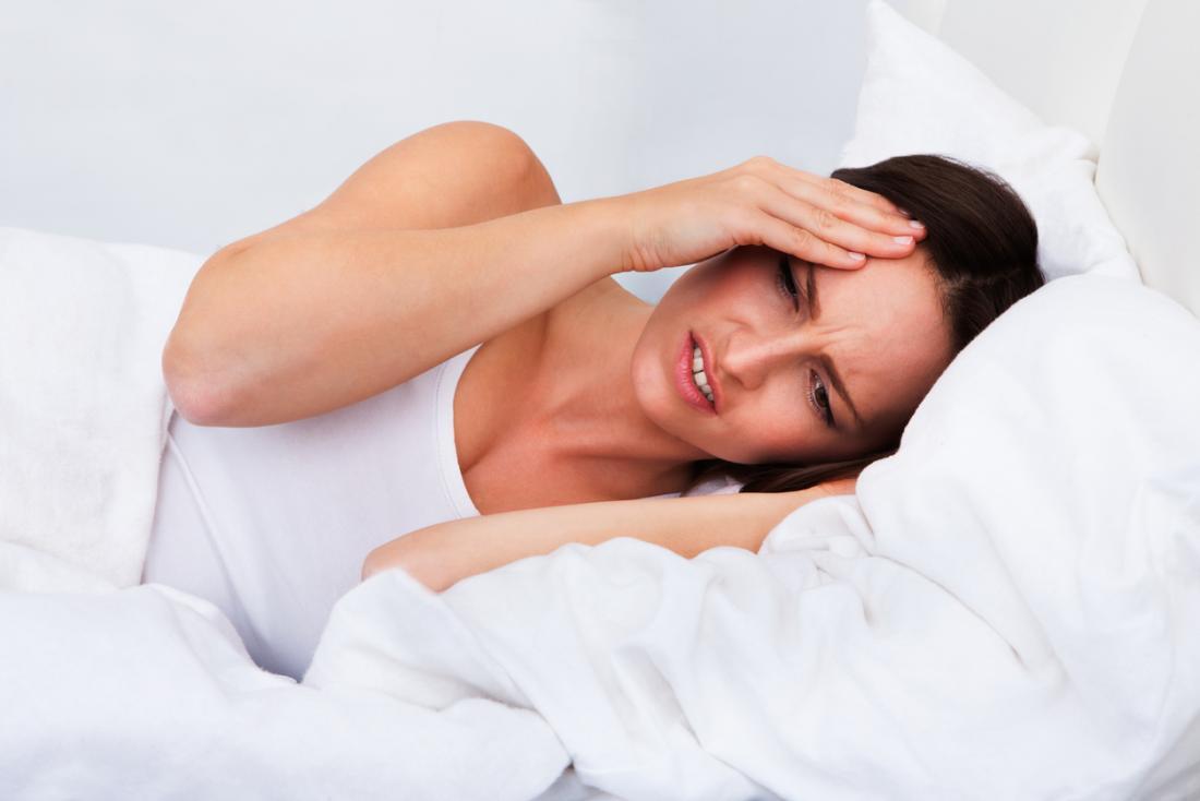 頭痛のあるベッドの女性
