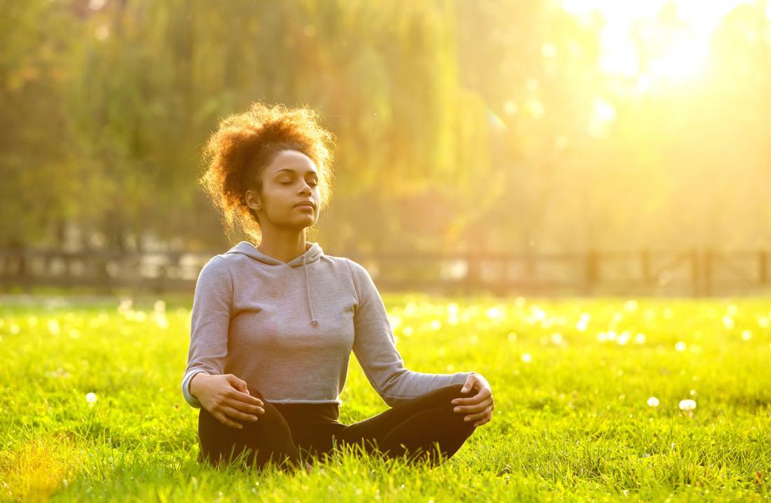 草の上で瞑想する女性