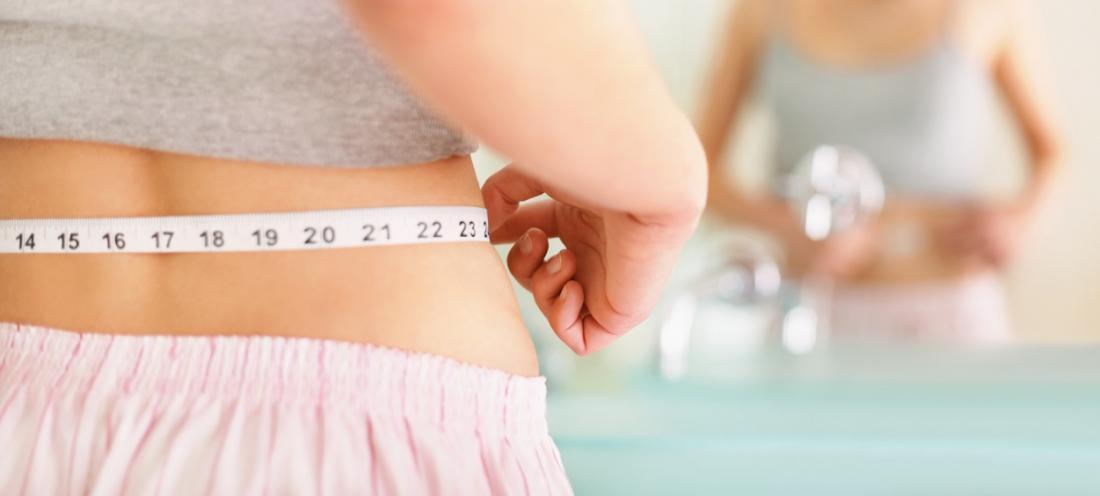 mulher, medindo sua cintura