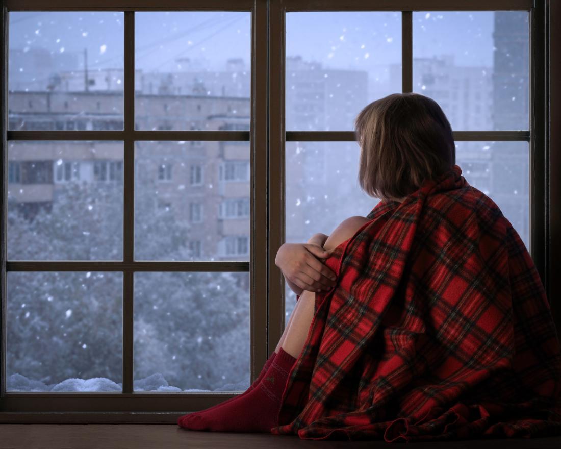 cô gái nhìn ra ngoài cửa sổ trên tuyết