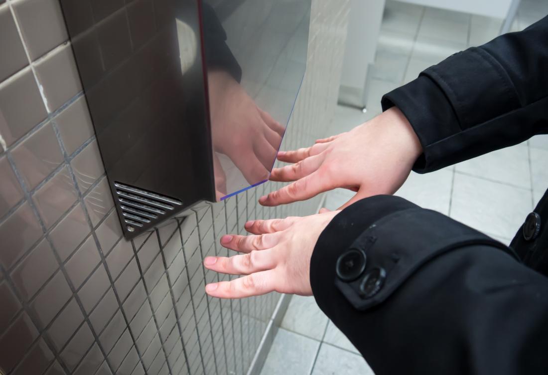 adam ellerini bir hava kurutma makinesi altında kurutma
