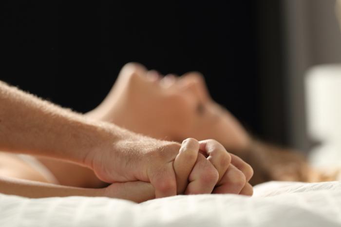 [Kobieta na łóżku trzymając się za ręce ze swoim partnerem]