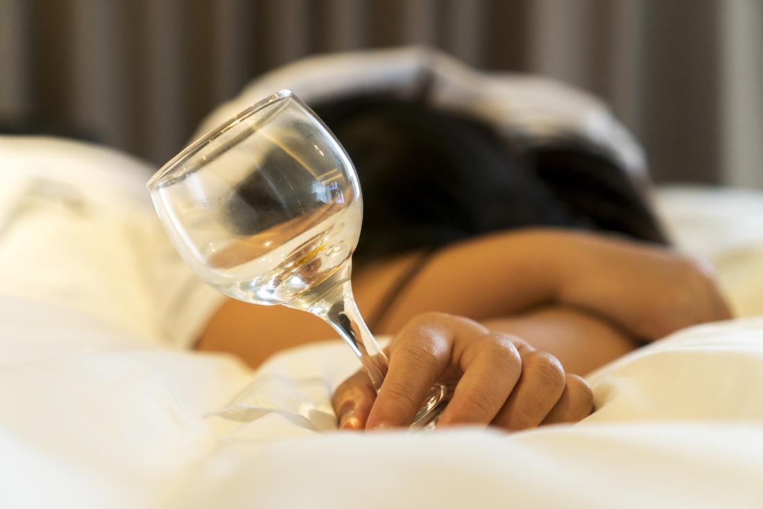 người phụ nữ ngủ với ly trống