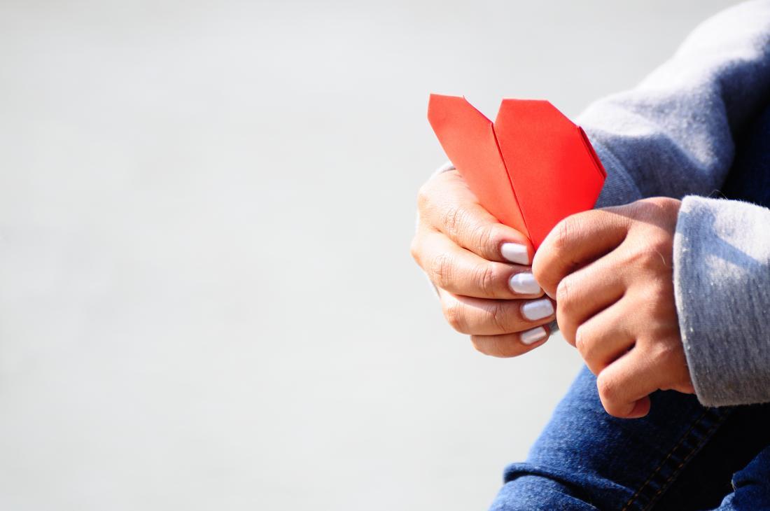 mulher segurando coração de papel