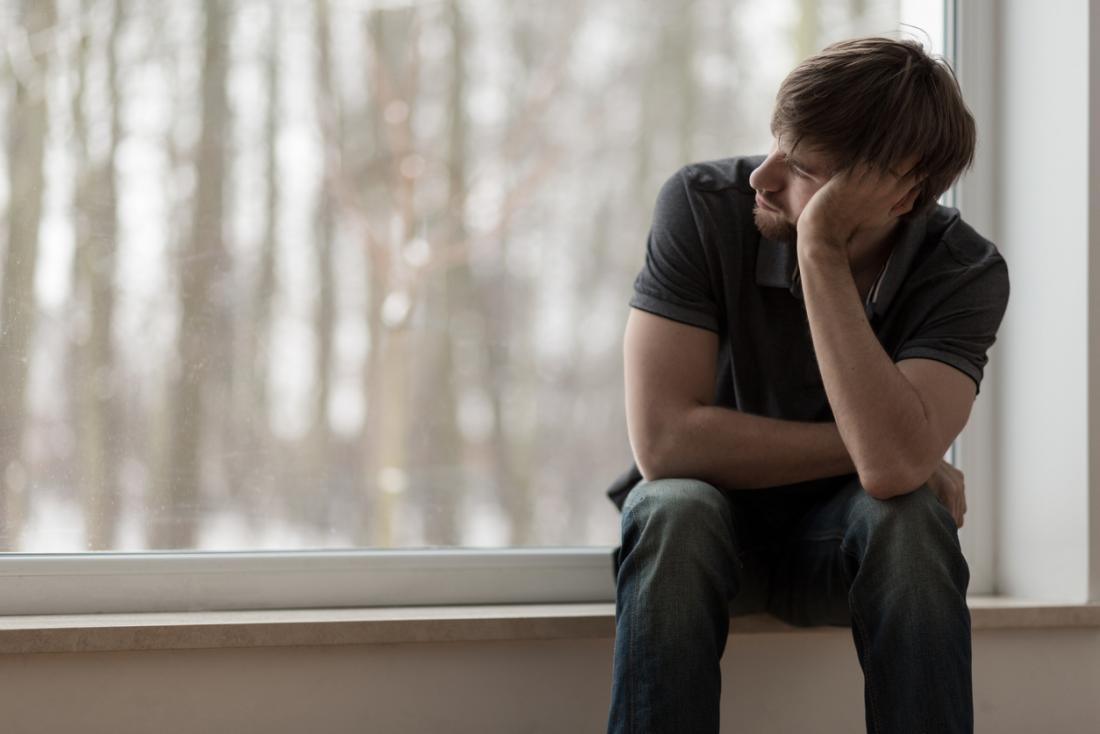 Sorunlu genç adam pencereden dışarı bakıyor
