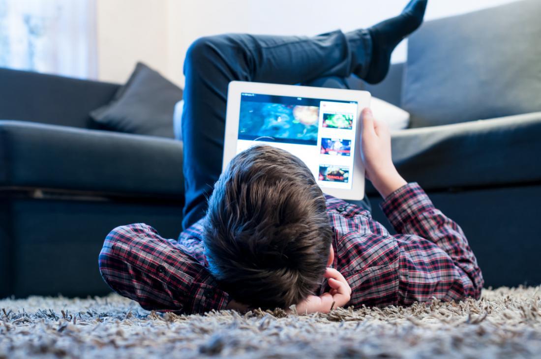 Junge, der auf den Fußboden mit einer digitalen Tablette legt
