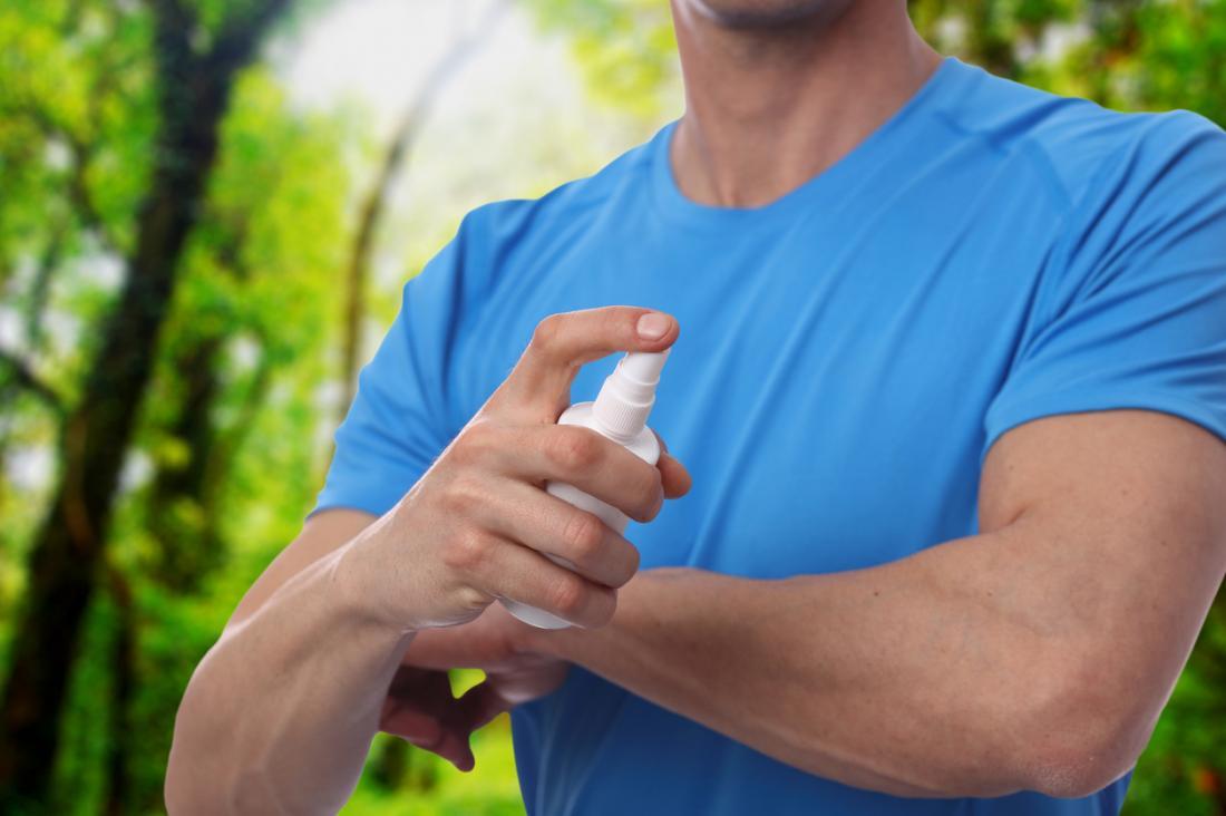 Mann, der Insekt oder Mückenschutz auf Arm spritzt.