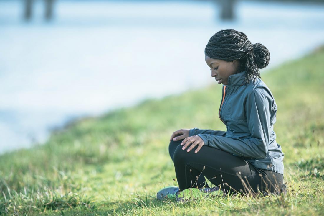 kobieta medytuje na trawie