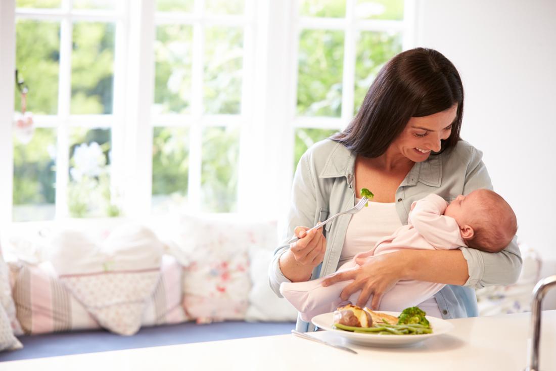 Người phụ nữ ăn bông cải xanh với một em bé
