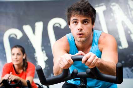 Người đàn ông và phụ nữ trên xe đạp tập thể dục