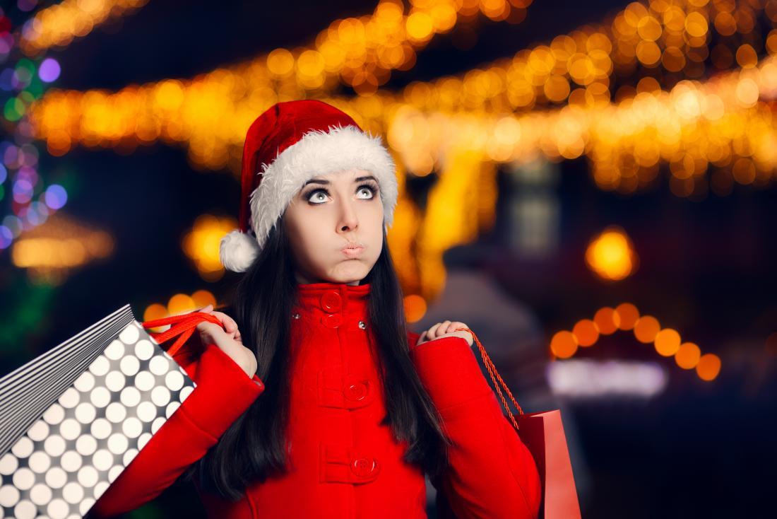 жена, облечена с коледна шапка и пазаруване