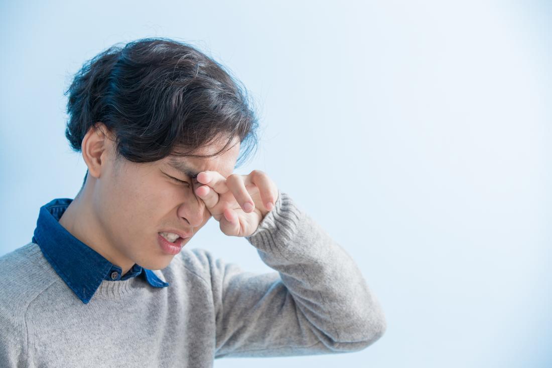 Homme avec un œil douloureux se demandant comment faire pour rincer vos yeux