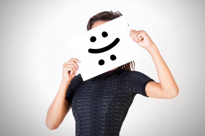 Eine Person, die ein glückliches trauriges Gesichtszeichen hält.
