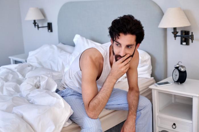 Ein ängstlicher Mann sitzt auf der Seite seines Bettes.