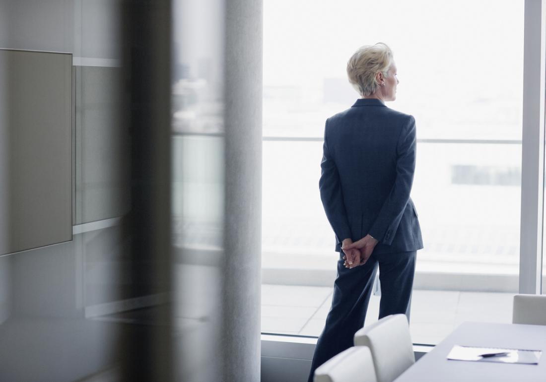 ältere Geschäftsfrau schaut aus dem Fenster