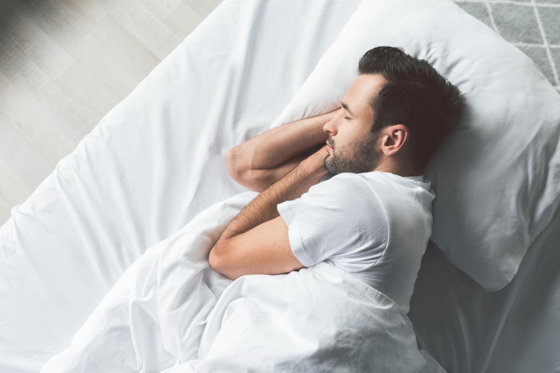 Човек спи в леглото