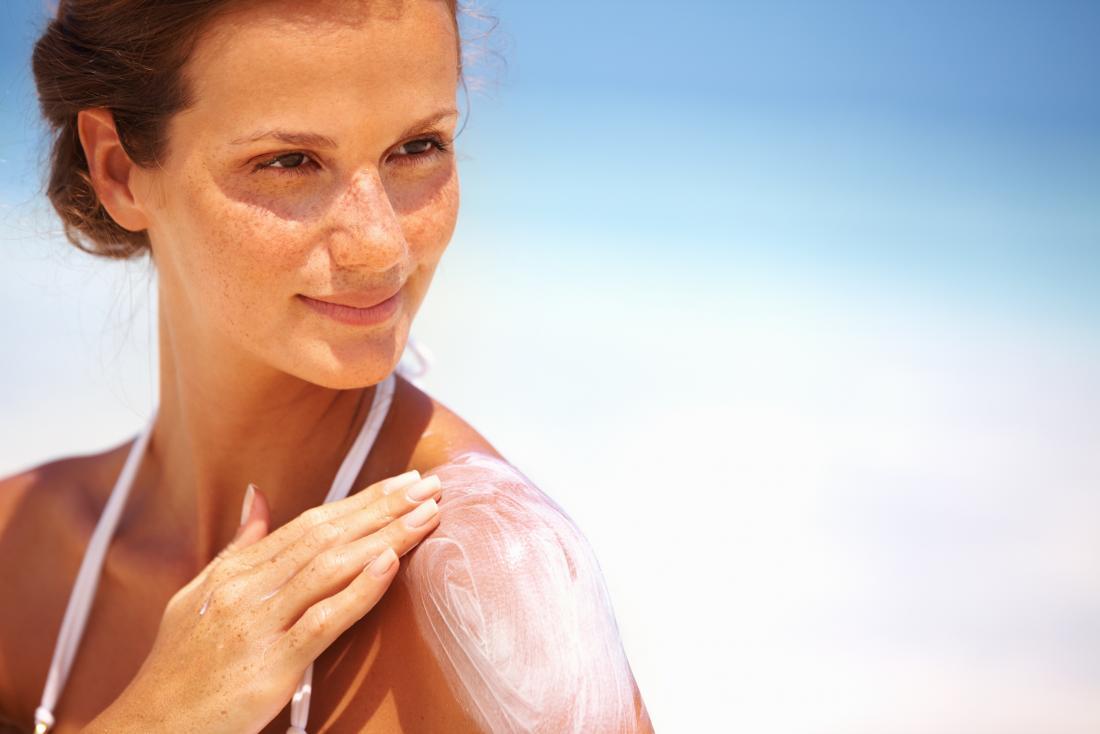 太陽の下の女性が日焼け止めローションを彼女の肌に塗布する。