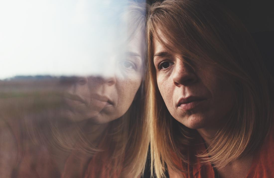 una donna triste che guarda fuori da una finestra